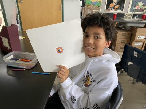 Student Andrew Gondry, freshman, holds up the beginning of his Mandala